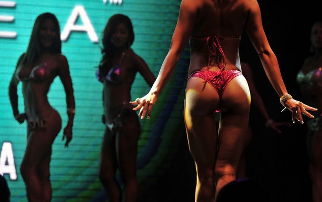 Women body builders going on stage during the Muscle Mania Fitness Korea Competition in Seoul, on October 3, 2013. Chosen bodybuilders from the competition will be able to participate in the Fitness Universe Competition in the next year. (Photo by Truth Leem/AFP Photo)