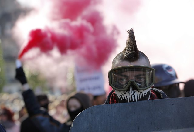 A man wears goggles as he walks near a safety flare during a demonstration to mark the one-year anniversary of a protest march in 2014 which ended in clashes with riot police, in Nantes February 21, 2015. (Photo by Stephane Mahe/Reuters)