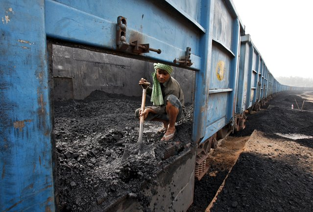 A worker unloads coal from a goods train at a railway yard in Chandigarh, India, in this July 8, 2014 file photo. (Photo by Ajay Verma/Reuters)