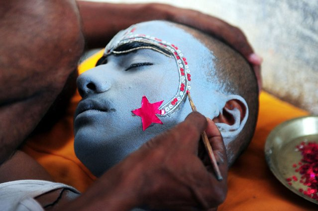 An Indian man applies make-up on a boy dressed as Hindu God Rama ahead of a religious procession during the Dussehra festival in Allahabad, on Oktober 10, 2013. (Photo by Sanjay Kanojia/AFP Photo)