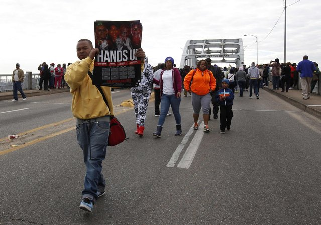 Thaddeus Jackson sells t-shirts as he walks along the Edmund Pettus Bridge before the beginning of the 50th anniversary of the Selma to Montgomery civil rights march in Selma, Alabama March 8, 2015. REUTERS/Tami Chappell  (UNITED STATES - Tags: POLITICS ANNIVERSARY SOCIETY)