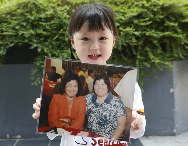 Jie Yie, four years old, holds a picture of her grandmother Lee Sew Chu and her aunt Ng May Li who were aboard missing Malaysia Airlines flight MH370, on the one year anniversary of its disappearance at a remembrance event, in Kuala Lumpur, March 8, 2015. Malaysia's Prime Minister Najib Razak said on Sunday Malaysia remains committed to the search for the missing MH370 jetliner a year after it vanished without trace and he is hopeful it will be found. REUTERS/Olivia Harris (MALAYSIA - Tags: TRANSPORT DISASTER ANNIVERSARY)