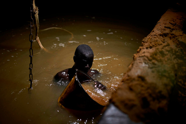 A Malian digger dives in the waters of the Niger River to check the quality of the sand, at a sand quarry near Kangaba in Mali' s southwestern Koulikoro region, on October 3, 2018. (Photo by Michele Cattani/AFP Photo)