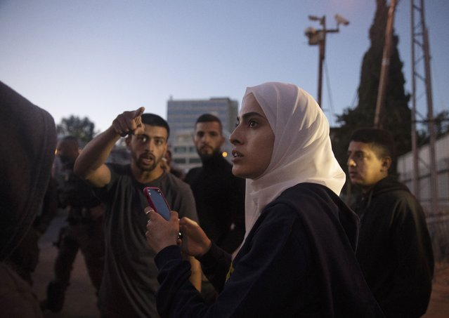 Palestinian activist Muna al-Kurd, center, stands with other activists as Israeli police approach their friends repairing a mural that was defaced by a Jewish settler, in the Sheikh Jarrah neighborhood of east Jerusalem, where Palestinian families face imminent eviction from their homes by Israeli settlers, Monday, May 24, 2021. On Sunday, June 6, 2021, Israel arrested and later released al-Kurd in the contested Sheikh Jarrah neighborhood of Jerusalem, a day after forcefully detaining a prominent journalist there. (Photo by Maya Alleruzzo/AP Photo)