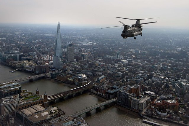 A Royal Air Force Chinook forms part of a flypast for a Service of Commemoration for Afghanistan, over London March 13, 2015. Queen Elizabeth and the Prime Minister, along with senior members of the royal family and of the government attended a service at St Paul's Cathedral to commemorate members of the armed forces who died during the 13 year Afghanistan war. (Photo by Carl Court/Reuters)