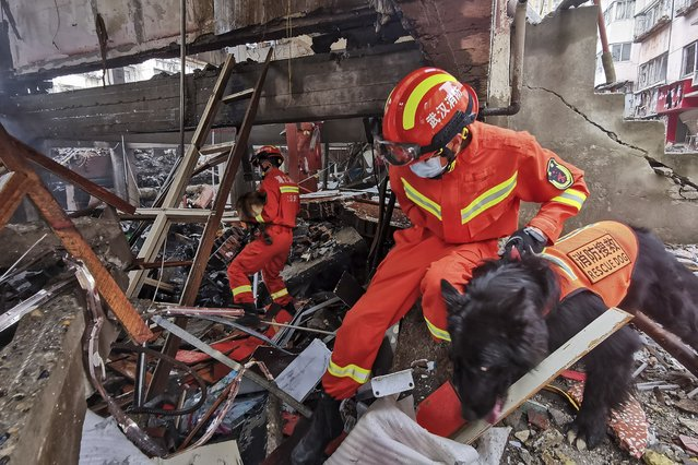In this photo released by Xinhua News Agency, rescue workers using sniffer dogs to search for survivors in the aftermath of a gas explosion in Shiyan city in central China's Hubei Province on Sunday, June 13, 2021. At least a dozen people were killed and more seriously injured Sunday after a gas line explosion tore through the residential neighborhood in central China. (Photo by Xiao Yijiu/Xinhua via AP Photo)