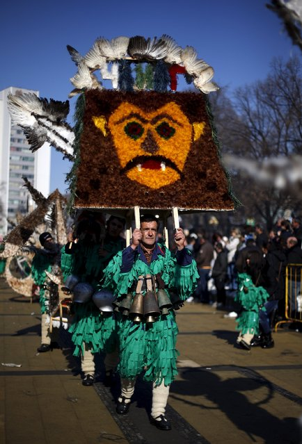 A participant dressed in traditional costume carries his mask during the International Festival of the Masquerade Games in the town of Pernik, Bulgaria January 30, 2016. (Photo by Stoyan Nenov/Reuters)