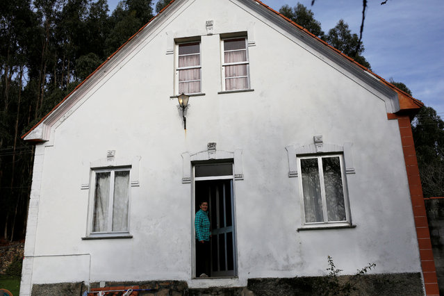 """Rosa Mosquera, 58, mother of Santi Diaz Mosquera, 41, a """"percebeiro"""" (barnacle fisherman), stands at the entrance of their house on the coast of Ferrol, in the northwestern Spanish region of Galicia, December 14, 2016. (Photo by Nacho Doce/Reuters)"""