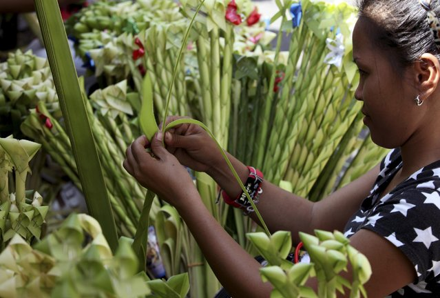A resident crafts palm fronds to be blessed for Palm Sunday rites among Roman Catholics at suburban Paranaque city, south of Manila, Philippines Saturday, March, 28 2015. (Photo by Bullit Marquez/AP Photo)