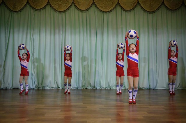 """In a photo taken on December 1, 2018 children perform with footballs at the Sinuiju City Kindergarten in North Korea's border city of Sinuiju. Lined up in vividly-coloured costumes, make-up and bright smiles, the children of the Sinuiju City Kindergarten belted out the finale of their hour-long show, """"We Cannot Live Without You, Father"""" – an ode to Kim Jong Un. (Photo by Ed Jones/AFP Photo)"""