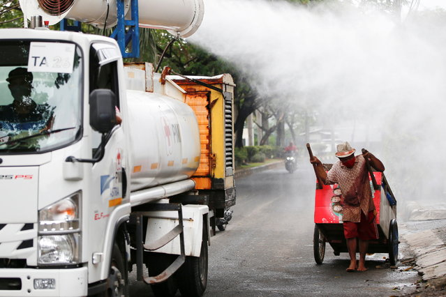 A man pulling a cart reacts as Indonesian Red Cross personnel spray disinfectant using a gunner around the Daan Mogot neighborhood, as the coronavirus disease (COVID-19) cases surge in Jakarta, Indonesia, June 30, 2021. (Photo by Willy Kurniawan/Reuters)