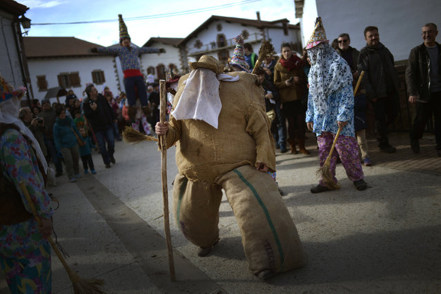 A person dressed as Ziripot, a traditional figure stuffed with straw, walks in front of the figure of Miel Otxin (seen behind with outstretched arms) alongside the Txatxos during carnival celebrations in the Navarran village of Lantz, February 8, 2016. The Ziripot's role as the strongest person in the village is to defeat the evil bandit Miel Otxin, while the Txatxos represent the population of Lantz. (Photo by Vincent West/Reuters)