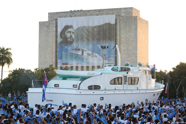 "An image of late Cuban President Fidel Castro hangs on a building as a replica of the Granma yacht passes by during a march to mark the Armed Forces Day and commemorate the landing of the Granma, which brought the Castro brothers, Ernesto ""Che"" Guevara and others from Mexico to Cuba to start the revolution in 1959, in Havana, Cuba, January 2, 2017. (Photo by Alexandre Meneghini/Reuters)"