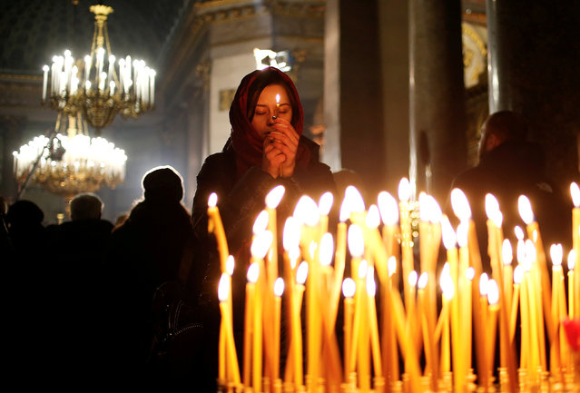 A woman prays during the Orthodox Christmas service at Kazan Cathedral in Saint Petersburg, Russia January 6, 2019. (Photo by Anton Vaganov/Reuters)