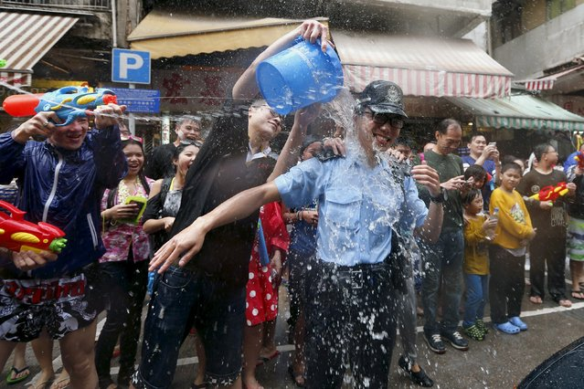 Water is thrown on a police at a water fight during Songkran Festival celebrations Kowloon City district, known as Little Thailand as there is large number of restaurants and shops run by Thais, April 12, 2015. (Photo by Tyrone Siu/Reuters)