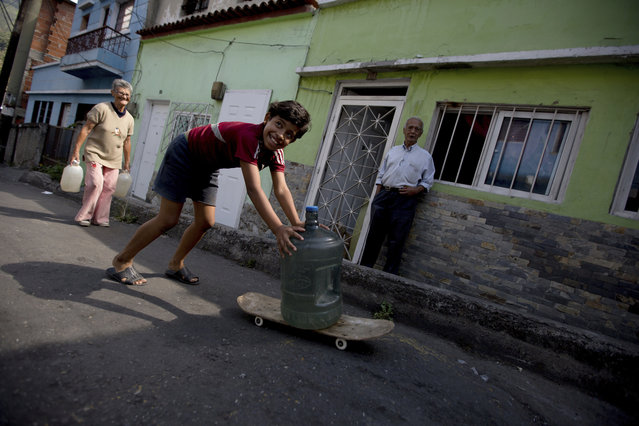 Cotiza neighborhood residents carry water from a public fountain a day after isolated protest against Venezuela's President Nicolas Maduro, in Caracas, Venezuela, Tuesday, January 22, 2019. Working class neighborhoods in Venezuela's capital sifted through charred rubble and smoldering trash on Tuesday, following a day of violence erupting in the streets. (Photo by Fernando Llano/AP Photo)