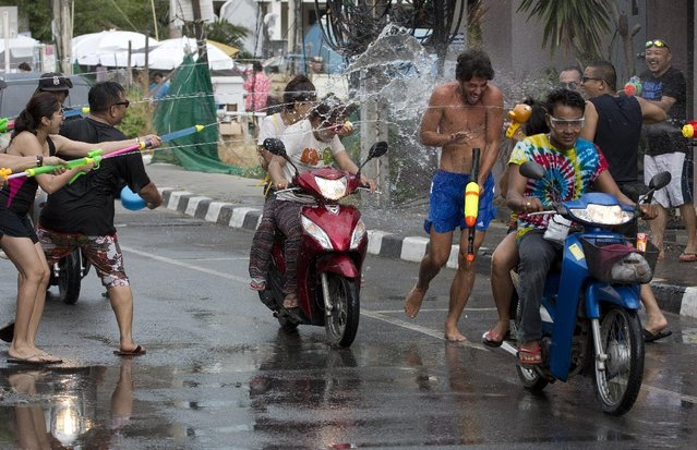 A tourist tries to escape as water is fired at him during the Songkran festival to celebrate the Thai New Year on  Samui Island in Surat Thani province, Thailand, Monday, April 13, 2015. (Photo by Mark Baker/AP Photo)