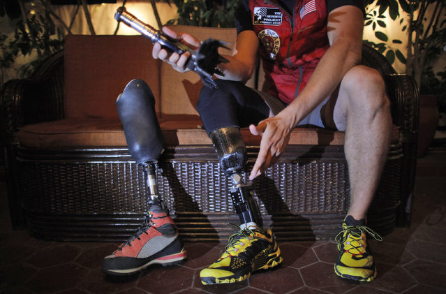In this Thursday, April 16, 2015 photo, former U.S. Marine Charlie Linville holds his prosthesis during an interview with the Associated Press in Kathmandu, Nepal. Former Staff Sgt. Linville, 29, from Boise, Idaho, who lost his right leg and several fingers in an explosion in Afghanistan is making a second attempt to scale Mount Everest to inspire others like him, a year after an avalanche that killed 16 Sherpa guides stopped him at the base camp. (Photo by Niranjan Shrestha/AP Photo)