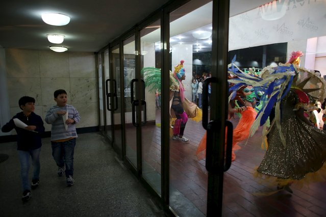 """Boys watch dancers who perform outside a cinema where the """"Cuerda Viva"""" (Live Strings) alternative music festival is taking place, in Havana, February 26, 2016. (Photo by Alexandre Meneghini/Reuters)"""