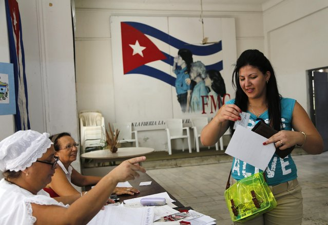 A woman holds her papers to be checked by electoral officials before casting her ballot during Cuba's municipal elections outside a polling station in Havana, Cuba, Sunday, April 19, 2015. (Photo by Desmond Boylan/AP Photo)