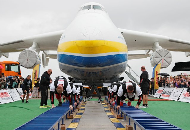 Ukrainian strongman athletes attempt to set a world record for pulling the world's largest cargo plane Antonov An-225 Mriya at an airfield in the settlement of Hostomel outside Kyiv, Ukraine on August 26, 2021. (Photo by Gleb Garanich/Reuters)