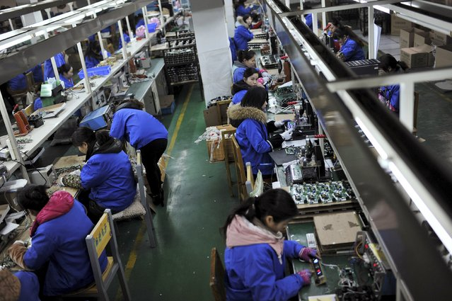 Employees assemble electronic components along a production line at a factory in Hefei, Anhui province, in this January 18, 2015 file photo. China's economy grew 7.0 percent in the first quarter of 2015, as expected but still its slowest rate in six years, reinforcing bets that policymakers will take more steps to bolster growth. Factory output climbed 5.6 percent in March 2015 from a year ago, below forecasts for a 6.9 percent gain. (Photo by Reuters/Stringer)