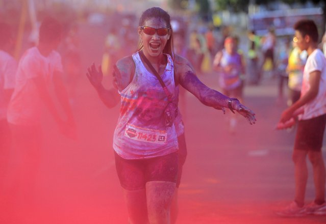 A jogger reacts as she runs through coloured powder thrown by race marshalls during the Manila Color Challenge in Pasay city, metro Manila April 19, 2015. (Photo by Romeo Ranoco/Reuters)