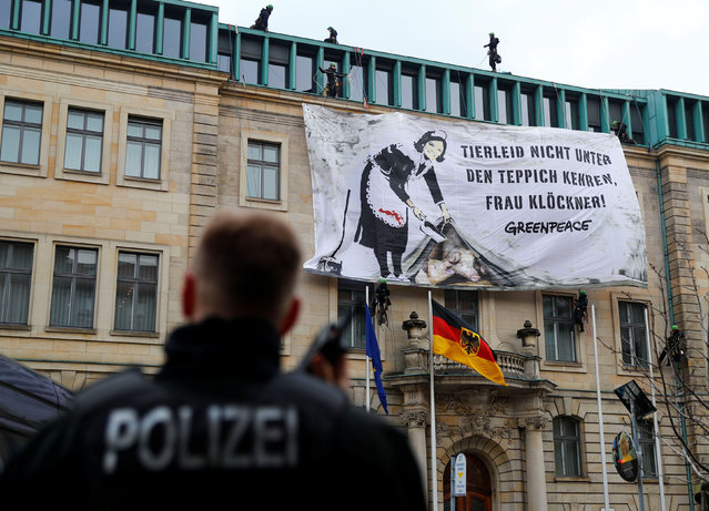 """A police officer uses his radio as Greenpeace activists unroll a placard on the facade of the Federal Ministry of Food and Agriculture to mark one year of Julia Kloeckner holding the ministerial post in Berlin, Germany, March 12, 2019. The banner reads """"Don't sweep the animal suffering under the carpet, Mrs. Kloeckner!"""". (Photo by Fabrizio Bensch/Reuters)"""