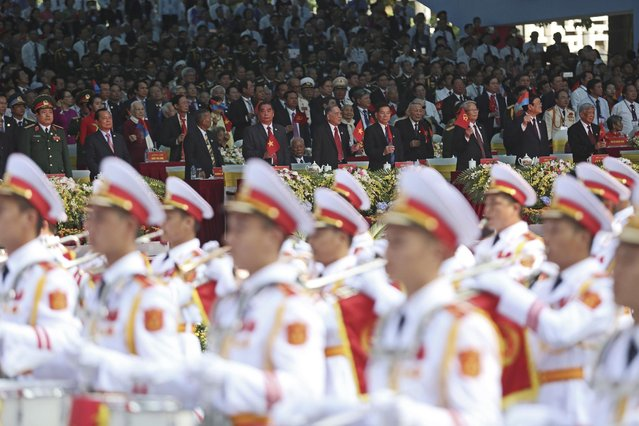 Vietnamese top leaders wave flags to the march during a parade celebrating the 40th anniversary of the end of the Vietnam War which is also remembered as the fall of Saigon, in Ho Chi Minh City, Vietnam, Thursday, April 30, 2015. (Photo by Na Son Nguyen/AP Photo)