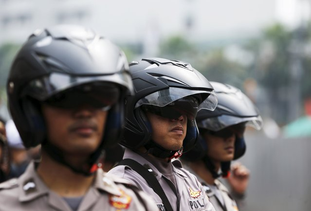 Policemen stand guard in front of the Presidential palace as workers hold a protest during a May Day rally in Jakarta, Indonesia, May 1, 2015. (Photo by Reuters/Beawiharta)