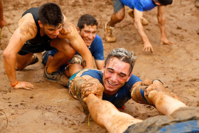 "Participants help each other to climb a 10km muddy obstacle course during the ""Run Mud"" race, on March 29, 2019 in the Israeli mediterranean coastal city of Tel Aviv. (Photo by Jack Guez/AFP Photo)"