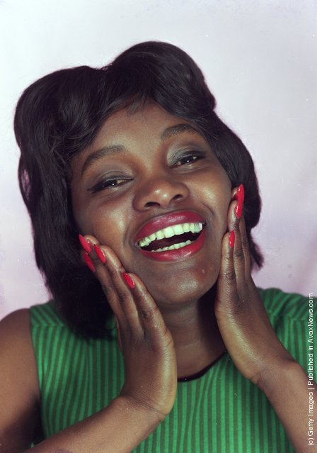 1964:  A delighted Nigerian woman models red nail varnish and matching lipstick