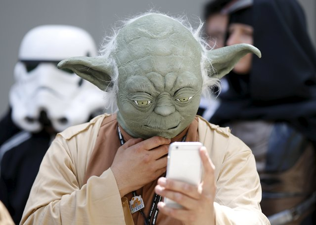 A cosplayer dressed as Star Wars character Yoda looks at a mobile phone at a Star Wars Day fan event in Tokyo May 4, 2015. (Photo by Toru Hanai/Reuters)