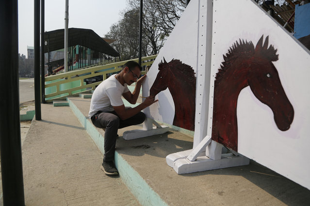 In this March 24, 2019, photo, a Nepalese army soldier draws a picture of horse for the Ghode Jatra festival in Kathmandu, Nepal. (Photo by Niranjan Shrestha/AP Photo)