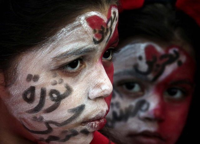 """Girls, with their faces painted in national colors, participate in a march for democracy in Manama, Bahrain, on February 11, 2014. Protesters chanted anti-government slogans during one of several protests organized in the run-up to Friday's third anniversary of an uprising demanding democracy in the Gulf island kingdom. Writing on the girls' faces reads """"Bahrain, the revolution continues"""" and """"Bahrain, revolution until victory"""". (Photo by Hasan Jamali/Associated Press)"""