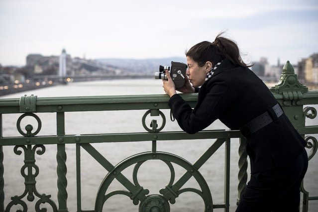Camerawoman Eszter Csepeli makes a record of the capital with an old Super 8 camcorder on Liberty Bridge in Budapest, Hungary, 05 March 2016. (Photo by Bea Kallos/EPA)
