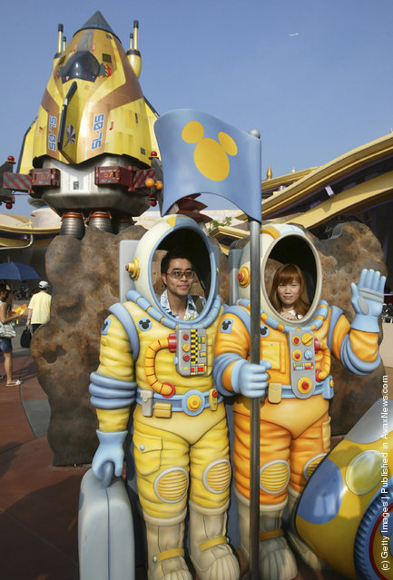 Tourists pose for pictures with decorations featuring space suits at the Tomorrow World in the Hong Kong Disneyland