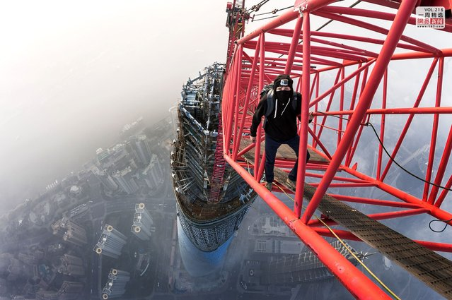Masked climber Vadim Makhorov on a crane atop the Shanghai Tower following the two-hour ascent. (Photo by Vitaly Raskalov/Caters News Agency)
