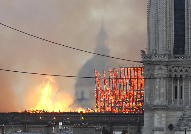Flames rise from Notre Dame cathedral as it burns in Paris, Monday, April 15, 2019. Massive plumes of yellow brown smoke is filling the air above Notre Dame Cathedral and ash is falling on tourists and others around the island that marks the center of Paris. (Photo by Thibault Camus/AP Photo)