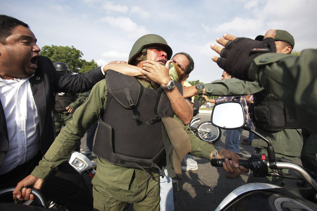 Opponents to Venezuela's President Nicolas Maduro, behind and left, scuffle with a Bolivarian National Guard officer who is loyal to President Nicolas Maduro during clashes with rebel soldiers and anti-government protesters outside La Carlota military airbase in Caracas, Venezuela, Tuesday, April 30, 2019. (Photo by Boris Vergara/AP Photo)