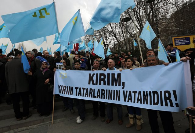 "Turks of Crimean Tatar origin waves  Crimean flags and hold a banner that reads ""Crimea is the homeland of Crimean Tatars"" as they demonstrate to protest against Russia's military intervention in Crimea, Ukraine, in Ankara, Turkey, Sunday, March 2, 2014. (Photo by Burhan Ozbilici/AP Photo)"