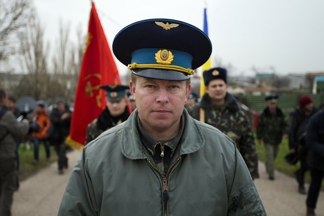 Col. Yuri Mamchur, commander of the Ukrainian garrison at the Belbek air base, lead his men to the base outside Sevastopol, Ukraine, Tuesday, March 4, 2014. Russian troops, who had taken control over Belbek airbase, fired warning shots in the air as around 300 Ukrainian officers marched towards them to demand their jobs back. (Photo by Ivan Sekretarev/AP Photo)