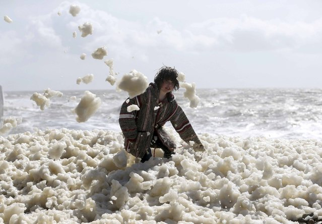 Max Butler-Cole, aged 9, plays in foam during stormy weather at Newhaven beach in southern Britain March 28, 2016. (Photo by Neil Hall/Reuters)