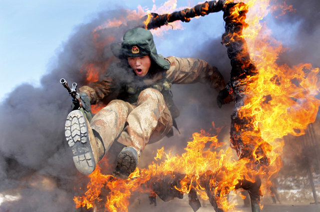 A frontier soldier from the People's Liberation Army jumps through a ring of fire as part of training in Heihe, Heilongjiang province, March 5, 2014. (Photo by Reuters/China Daily)