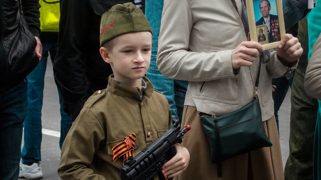 Children carrying guns and flags or wearing Soviet-style uniforms have become a common sight at Victory Day parades and other events in Russian-controlled Crimea. Russian and Ukrainian human rights activists have warned that such displays point to a growing trend of promoting Russian patriotism among kids on the Crimean peninsula, annexed from Ukraine in 2014. Alongside public events, many schools offer paramilitary classes, and children from age 8 are invited to enroll in Yunarmiya, a Russian patriotic youth movement. Here: A young participant carries a toy gun in Sevastopol, Crimea, during the Immortal Regiment march on Victory Day, observed on May 9, 2019. (Photo by Radio Free Europe/Radio Liberty)