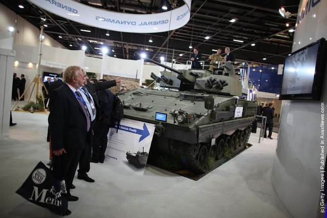 Visitors look at a General Dynamics Scout Special Vehicle on display at the Defence and Security Exhibition