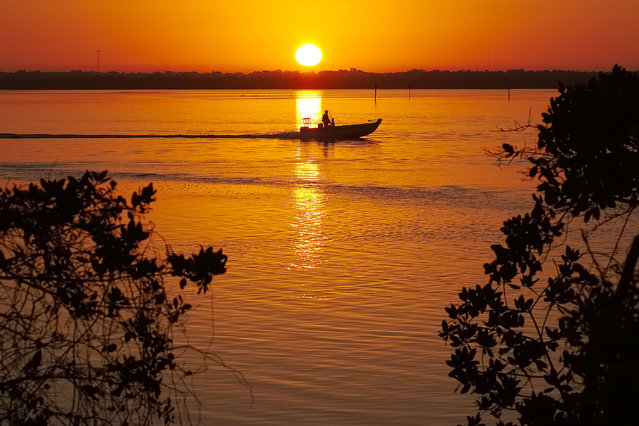 A boater cruises at sunrise near Bonita Springs, Fla., where temperatures in the area are expected to reach 80 degrees, Tuesday morning, March 4, 2014. (Photo by J. David Ake/AP Photo)