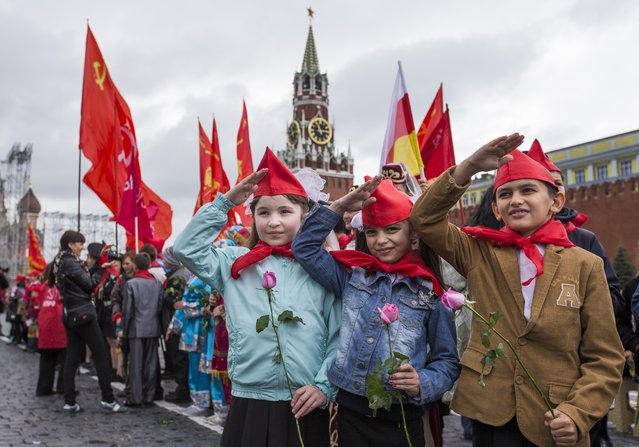 Girls and boys stand holding red neckerchiefs salute on Red Square, in front of the Spasslaya Tower, during a ceremony to celebrate joining the Pioneers organization, in Moscow, Russia, Sunday, May 17, 2015. (Photo by Alexander Zemlianichenko Jr./AP Photo)