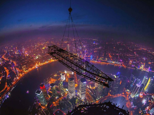 Cranes that have helped to build the Shanghai Tower, China's tallest building and the world's 2nd tallest, are seen being dismantled. (Photo by Rex Features)