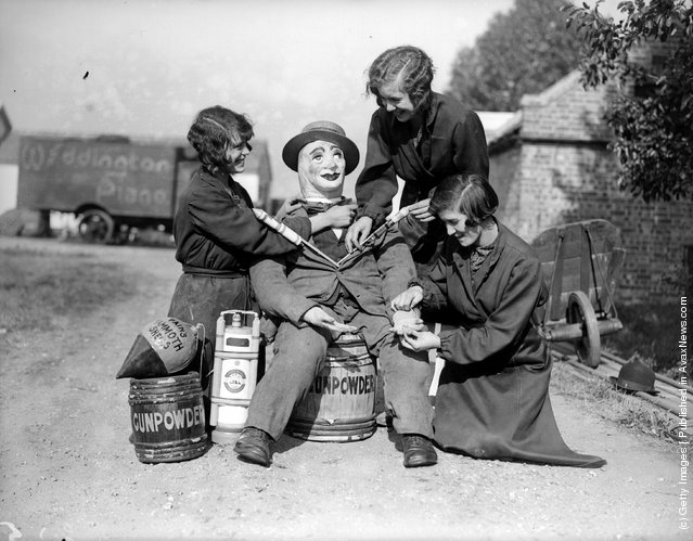 1929: Three young women preparing a guy. They are sitting him on a keg labelled gun powder